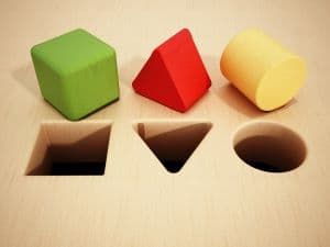 Round, square and triangular holes with coresponding colourful shapes