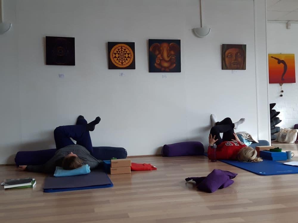 Two yoga students in Eye of the Needle using the wall as support.
