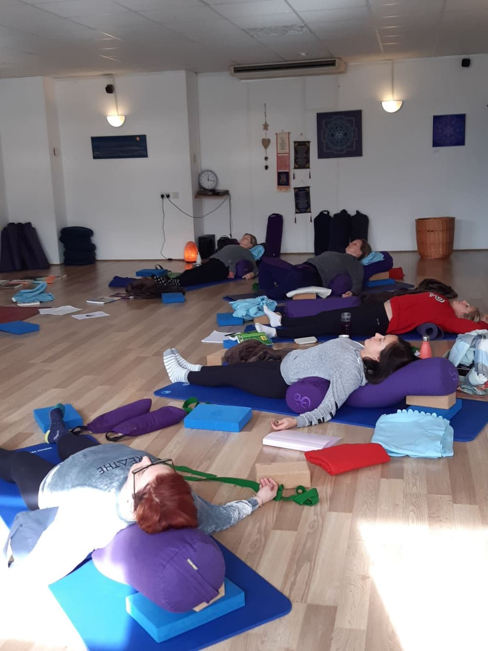 Group of yoga students in a supported fish pose in a Yin Yoga class.